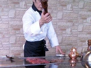 神蔓鉄板で肉を焼くシェフ